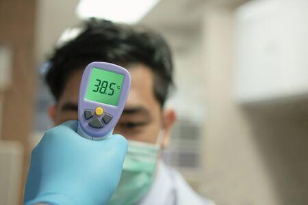 Medical staff using a thermometer gun machine check body temperature