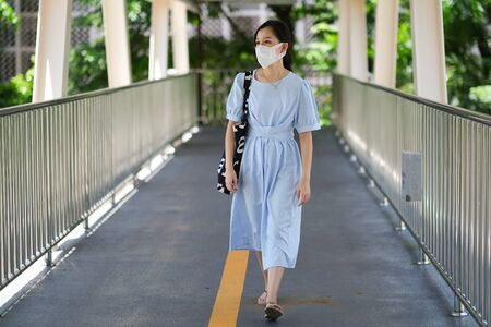 Asian girl wear surgical mask to protect the Covid-19 virus in public areas, New normal lifestyle