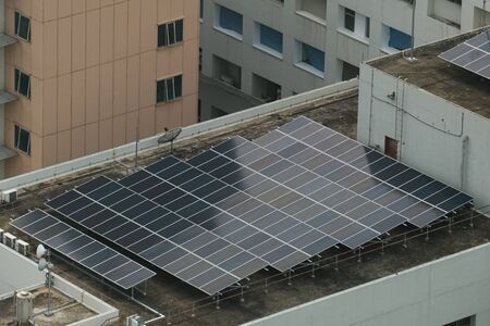 Solar power generation panels are installed on the roof of buildings in the city