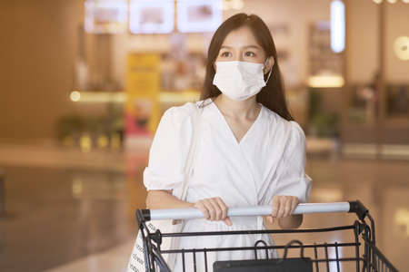 Asian girl wear surgical mask to protect the Covid-19 in supermarket, New normal lifestyle Stockfoto
