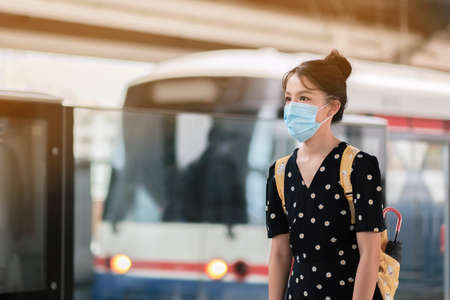 Asian travelers girl in train station with medical face mask to protection the Covid-19, new normal lifestyle