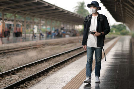 Asian travelers men and camera in train station with medical face mask to protection the Covid-19, new normal lifestyle