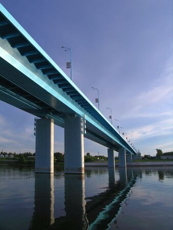 bridging: The photo of the bridge through the river Volga in Russia, is a modern construction bridging shores under a palate           Stock Photo