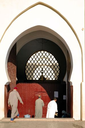 believers: Morocco, Marrakech, Marrakesh: White wall; typical round door and believers going to the prayer
