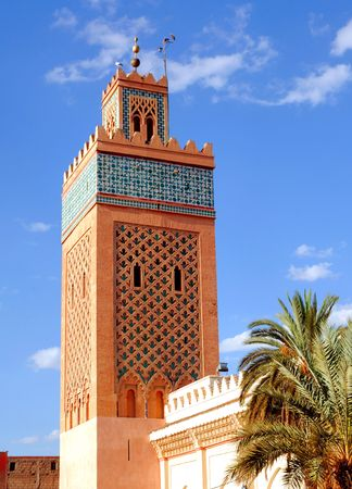 minaret: Morocco, Marrakech, Marrakesh: The Koutoubia mosque; Blue sky and palm trees framed the red and blue minaret; a typical view of Marrakesh
