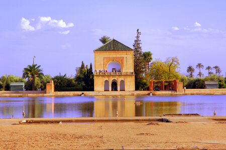 Morocco, Marrakech: blue sky and the blue water of the typical pond framed this view of the bungalow of the famous Menara garden; a typical landscape