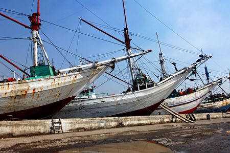 drydock: Indonesia, Jakarta: boats at Sunda Kelapa an ancient sea port; one of the most famous for the construction of the traditional wood boats; blue sky and colorful big wood boats Stock Photo