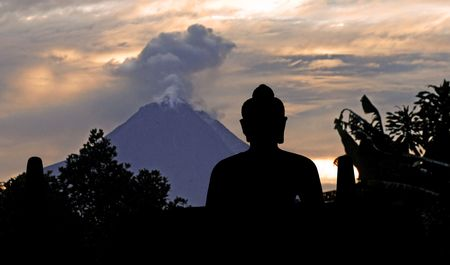 borobudur: Indonesia, java, Borobudur: Indonesia, java, Borobudur: a beautifull stone seat buddha in meditation facing to the  sunrise and to the merapi , the most dangerous indonesian volcano Stock Photo