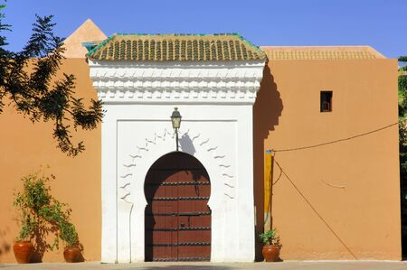 Morocco, Marrakesh, Marrakech: blue sky and a traditional brown door framed by a carved white wall near the  Koutoubia mosque photo