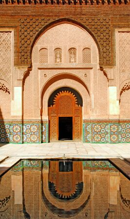 Morocco, Marrakech: Ben Youssef madrasa an ancient koranic school; architectural detail of the main entrance; nice traditional door framed by a  white carved stone; a traditional pond complete this typical image