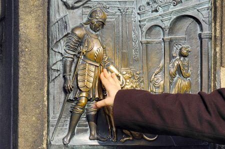 fidelity: Czech Republic, Prague: touching the sculpted door; a bronze panel representing an aristocratic scene with a dog. fidelity symbolism