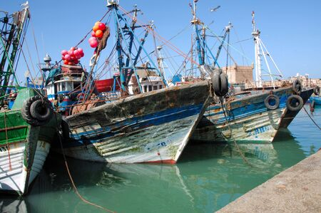Morocco, Essaouira:blue sky and blue fishing boats at the harbour photo