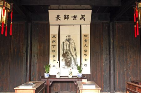China,suzhou:  typical chinese village house; an indoor view with wooden fourniture and a confucius representation   photo
