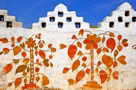 harmonious: India, Rajasthan, Jaisalmer: colourful painted walls in the villages near Jaisalmer; flowers and birds in harmonious and hot colors; womans work