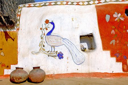 India, Rajasthan, Jaisalmer: colourful painted walls in the villages near Jaisalmer; flowers and birds in harmonious and hot colors; womans work  photo