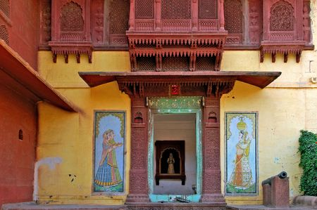 first floor: India, Jaisalmer: Indian palace architecture; red walls and wooden carved frame and window at the first floor; on the ground floor a beautiful window framed by two paintings Stock Photo