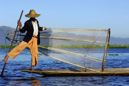 Myanmar, Inle Lake: blue sky and a  fishermen with a large hat on the lake paddling with the help of their leg
