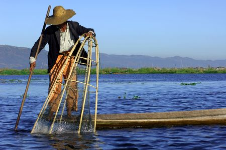 Myanmar, Inle Lake: blue sky and a  fishermen with a large hat on the lake paddling with the help of their leg Stock Photo - 2870864