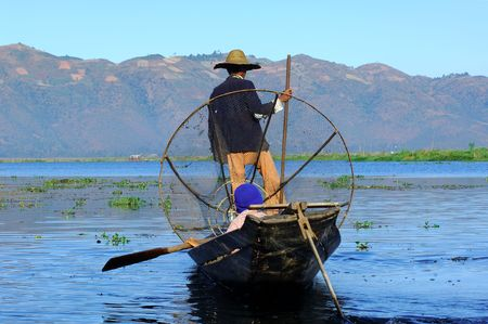 inle: Myanmar, Inle Lake: blue sky and a  fishermen with a large hat on the lake paddling with the help of his leg