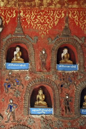 niches: Myanmar, Inle Lake: Shwe Yan Pyay monastery, small buddhas and candles inside the niches of a wall Stock Photo