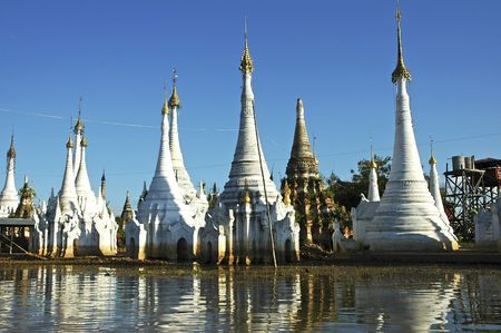 inle: Myanmar, Inle lake:  white stupas near the floating market and their shadows on the water Stock Photo