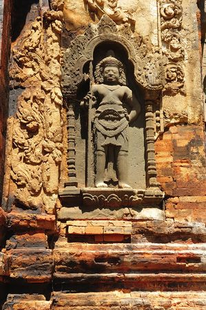 """nandi: In Cambodia in the ancient city of Roulos the Hindu temple of Preah Ko or"""" The sacred bull"""" was built in the 9th century by the king Indravarman. View of a carved wall with a khmer guardian"""