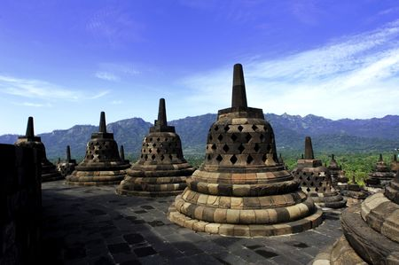 narrative: Indonesia, Central Java. The temple of Borobudur is a Mahayana Buddhist temple from the 9th century with a main shrine and several perforated stupas.