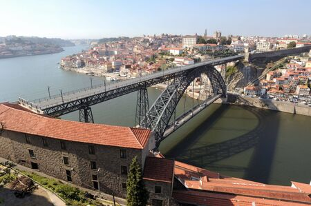 main river:  Portugal, Porto; view of the ancient city with is main river, the Douro and of the sunroofs of the famous oporto wine caves.  On the background the bridge Eiffel or D.Luis