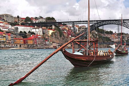 luis: Portugal, Porto; view of the ancient city with is main river, the Douro and the famous oport wine boats. On the background the bridge Eiffel or D.Luis