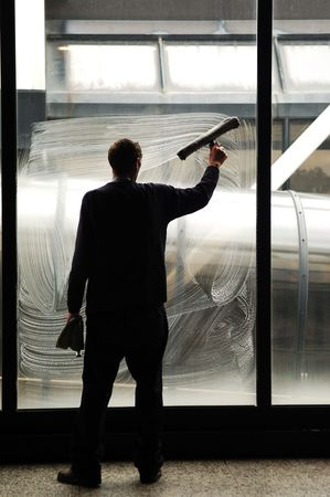 A worker cleaning the big windows of an airport