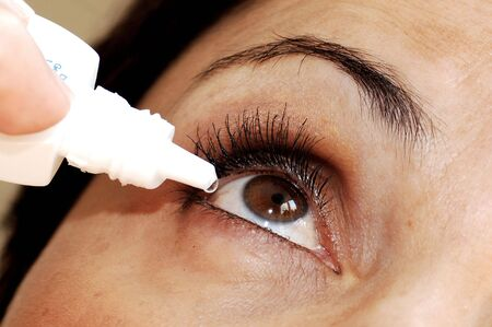 irritated: Putting eye drops into dry eyes