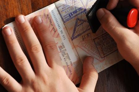 op maat: Immigratiecontrole; markering door stampen een passeport Stockfoto