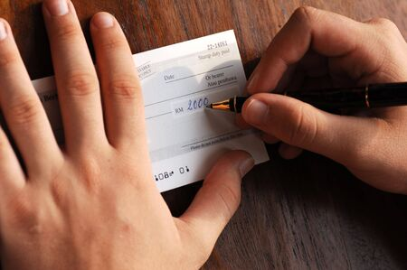 Writing a  bank check, paying bills Foto de archivo