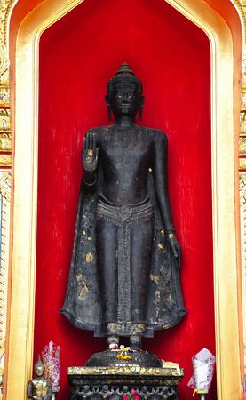 Thailand, the Wat Benchamabophit or the Marble temple in the city of Bangkok constructed in 1900 is faced with white Carrara marble.View of an outsider standing Buddha inside a red niche photo