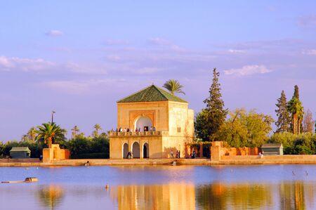 marrakesh: Marocco, Marrakech: cielo blu e l'azzurro delle acque del laghetto incorniciato tipici questo punto di vista del bungalow del famoso Menara giardino; un tipico paesaggio