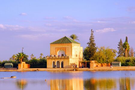 marrakech: Morocco, Marrakech: blue sky and the blue water of the typical pond framed this view of the bungalow of the famous Menara garden; a typical landscape