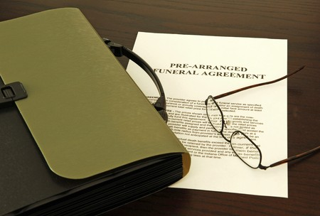 lost in thought: View of a funeral agreement with a green briefcase and glasses