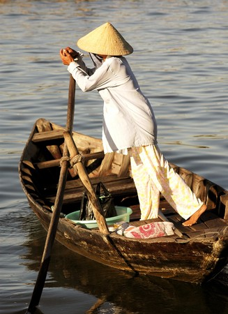 Sunny day and a woman driving a boat in the ancient city of Hoi An in Vietnam Foto de archivo