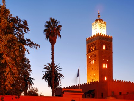 Morocco, Marrakech, Marrakesh: The Koutoubia at night; nice night view of the mosque, dark blue sky; palm trees and the illuminated minaret