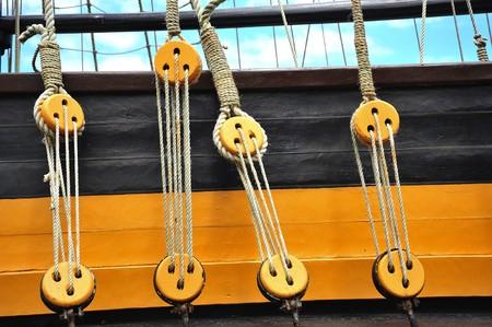 poleas: Cielo azul y una vista de un barco de poleas con una cuerda en el interior de la circunferencia de un viejo barco de madera de color amarillo