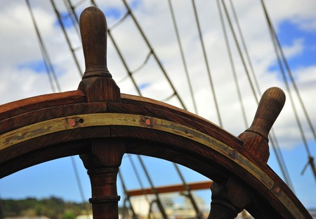 Blue sky and a view of the rudder-wheel of an old  wooden ship  Stock Photo