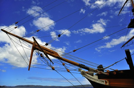 pulleys:  Blue sky and a view of the pulleys with a rope running inside the circunference of an old  wooden ship