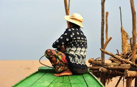 reps: Camboya, Siam Rep; vista del lago Tonle Sap en la final de la tarde. Cielo azul y un bote con una mujer camboyana