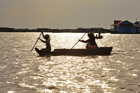 Cambodia, Siam Rep; view of the Tonle Sap lake in the end of the afternoon. Sun set and a boat with two Cambodian women photo
