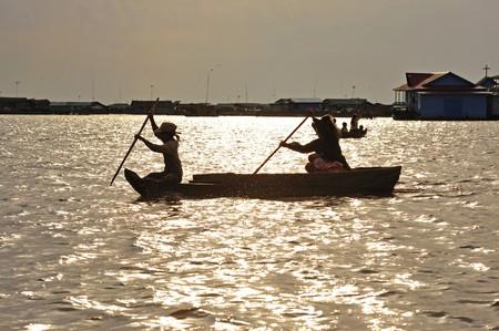 reps: Camboya, Siam Rep; vista del lago Tonle Sap en la final de la tarde. De sol y un barco con dos mujeres camboyanas