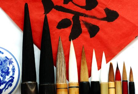 caligraphy: View of red paper and chinese black character with traditional caligraphys tools