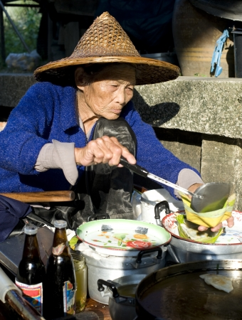 atraer: Tailandia, Bangkok: 100 km de Bangkok, Damnoen Saduak mercado flotante atraer cada d�a a cientos de turistas. Una mujer tailandesa preparar un plato tradicional. Foto de archivo