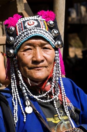 tribu: Tailandia, el retrato de una mujer Akha o kalo. Esta tribu vive en las monta�as de China, Laos, Myanmar y el norte de Tailandia. El tocado con hileras de perlas est� decorada con plata globs Foto de archivo