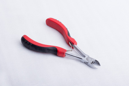A wire cutter with a black and red handle on a white surface