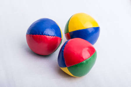 A set of three colorful juggling balls on a white surface.